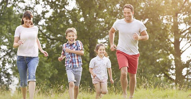 Familie läuft über eine Wiese